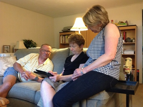 Phil, Virginia and Kathleen looking at pictures from cruise.